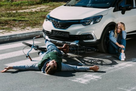 high angle view of cyclist lying on road and scared woman crying near car after traffic collision