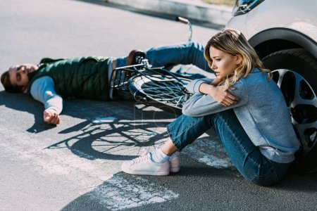 high angle view of young woman sitting near car and victim of car accident lying on road