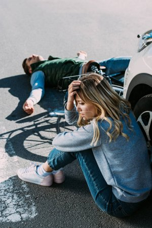 high angle view of young woman sitting near car after while cyclist lying on road after traffic collision