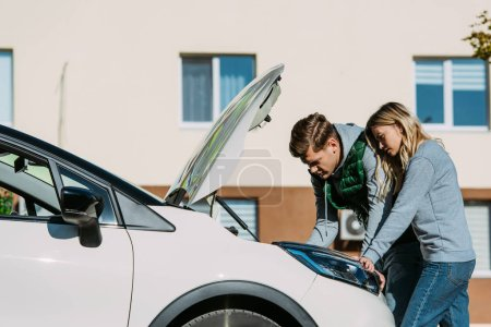 young couple repairing broken car on street