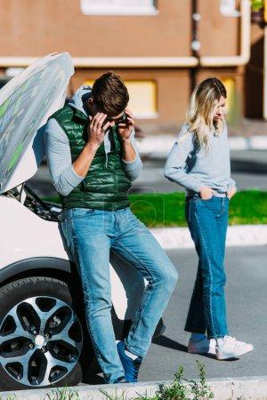 upset young man and woman near broken car on street