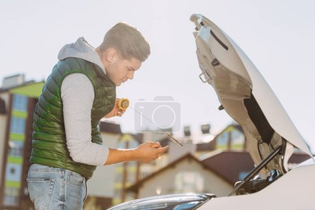 side view of young man checking engine oil level in broken car