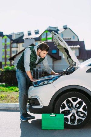 side view of focused young man repairing broken car on street