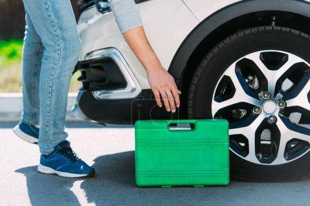 cropped shot of man holding toolbox while repairing broken car