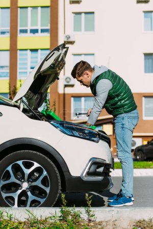 Photo for Side view of young man fixing broken car on street - Royalty Free Image