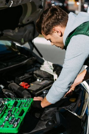 young man with toolbox fixing broken car engine