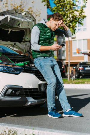 upset young man sitting on broken car and using smartphone