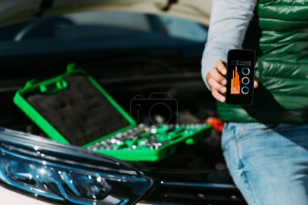 cropped shot of man holding smartphone with charts on screen while sitting on broken car with toolbox