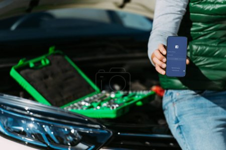Photo for Cropped shot of man holding smartphone with facebook app while sitting on broken car with toolbox - Royalty Free Image