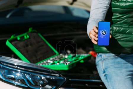cropped shot of man holding smartphone with shazam app while sitting on broken car with toolbox