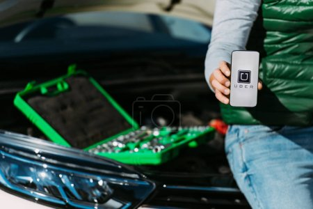 Photo for Cropped shot of man holding smartphone with uber app while sitting on broken car with toolbox - Royalty Free Image