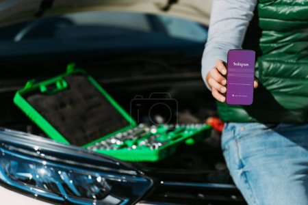 Photo for Cropped shot of man holding smartphone with instagram app while sitting on broken car with toolbox - Royalty Free Image