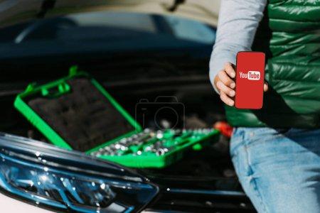 Photo pour Recadrée tir d'homme tenant le smartphone avec l'application youtube tout en étant assis sur la voiture avec la boîte à outils - image libre de droit