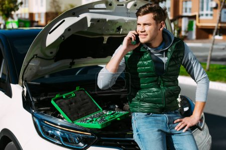 Photo for Smiling young man talking by smartphone while sitting on broken car - Royalty Free Image
