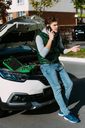 young man talking by smartphone while sitting on broken car