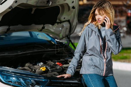 Photo for Upset young woman talking on smartphone and looking at engine while sitting on broken car - Royalty Free Image