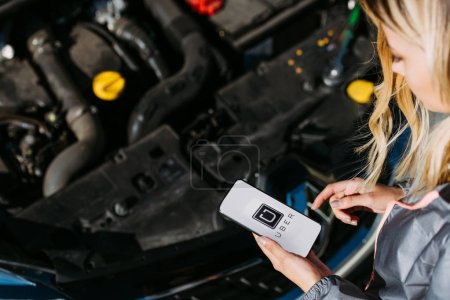 cropped shot of girl using smartphone with uber app while fixing broken car