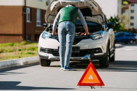 panneau de signalisation et vue arrière de l'homme, fixation voiture cassée sur route