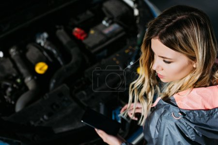 high angle view of young woman using smartphone with blank screen while repairing broken car