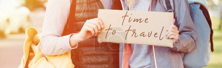 cropped shot of young couple with backpacks holding card with inscription time to travel
