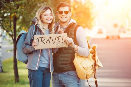 Photo for Happy young couple of travelers holding card with inscription travel and smiling at camera on road - Royalty Free Image