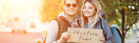Photo for Happy young couple of travelers holding card with inscription vacation time - Royalty Free Image