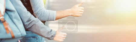 Photo for Cropped shot of young couple hitchhiking on road at sunset - Royalty Free Image