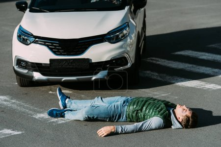 high angle view of injured young man lying on road after motor vehicle collision
