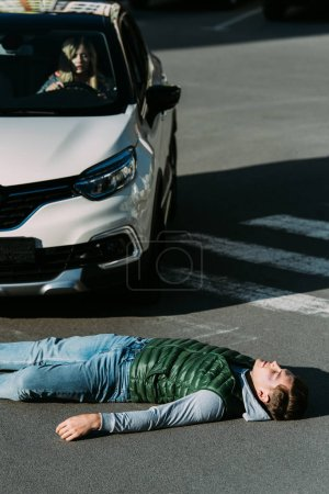 high angle view of injured young man lying on road after traffic collision