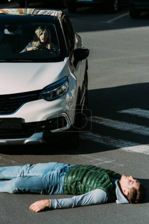 high angle view of injured young man lying on road after car accident