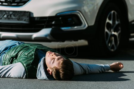 close-up view of injured young man lying on road after car accident
