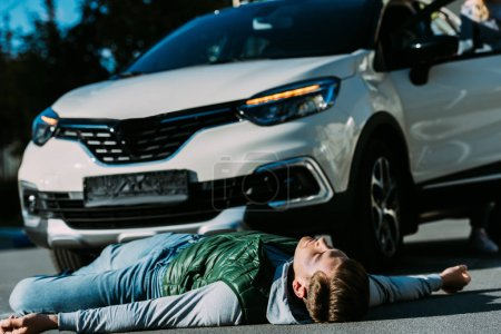 injured young man lying near car on road after traffic accident