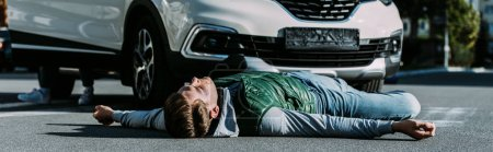 injured young man lying on road after car accident