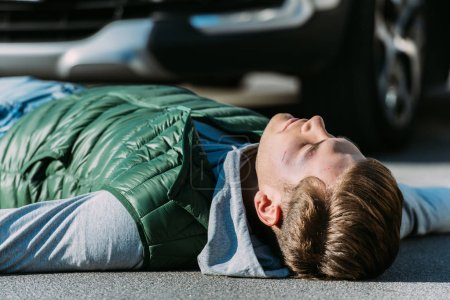 close-up view of injured young man lying on road after motor vehicle collision