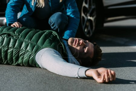 cropped shot of woman touching injured young man lying on road after car accident