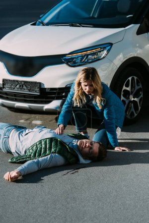 high angle view of young woman touching victim of motor vehicle collision