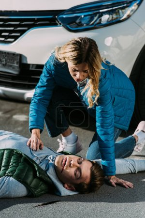 young woman checking heartbeat of victim after traffic collision