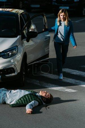 Foto de Mujer Mieda abrir la puerta del coche y va a joven herido tumbado en el camino después de accidente de tráfico - Imagen libre de derechos