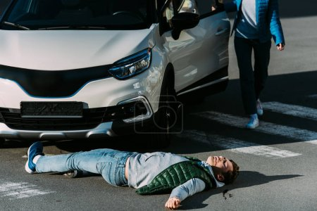 cropped shot of woman opening car door and going to injured man lying on road after car accident