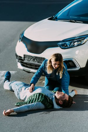 Foto de Vista de ángulo alto de mujer joven mirando tocar heridas hombre acostado en el camino después de accidente de tráfico - Imagen libre de derechos