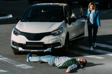 Photo pour Jeune femme, ouverture de porte de voiture et va blessé gisant sur la route après l'accident de voiture - image libre de droit