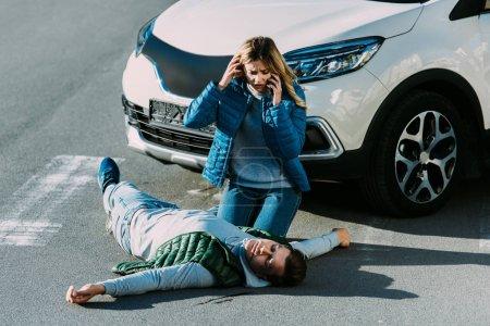 Foto de Vista de ángulo alto de Miedo mujer joven mirando hombre herido y llamar a la emergencia tras accidente de coche - Imagen libre de derechos