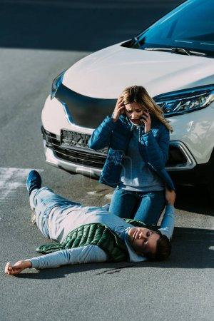 Photo pour Peur jeune femme regardant blessé et appeler d'urgence après l'accident de voiture - image libre de droit