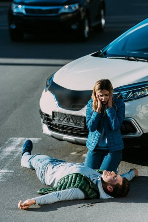 high angle view of scared young woman looking at victim lying on road after car accident