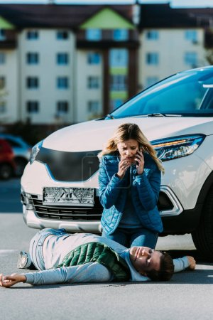 scared young woman calling emergency and looking at injured man lying on road after traffic collision
