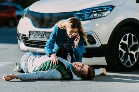 scared young woman calling emergency and looking at injured man on road after traffic accident