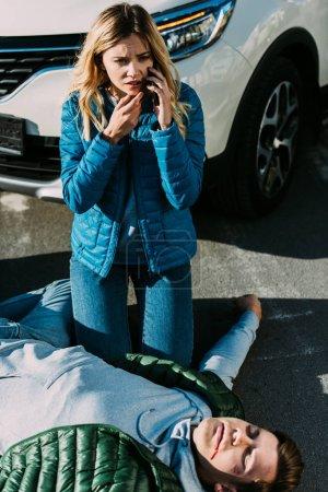 Photo pour Vue d'angle élevé de peur jeune femme l'appel d'urgence alors que l'homme blessé gisant sur la route après l'accident de la circulation - image libre de droit