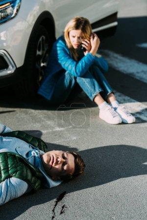 Photo pour Vue d'angle élevé de peur jeune femme l'appel d'urgence alors que l'homme blessé gisant sur la route après collision du trafic - image libre de droit