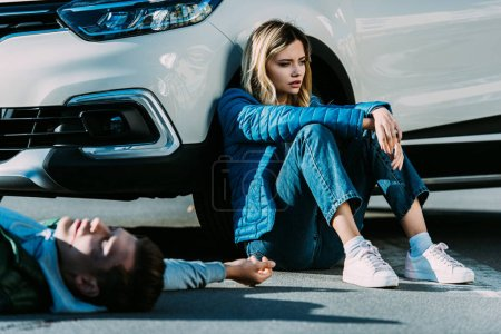 scared young woman sitting near car and injured man lying on road after traffic collision