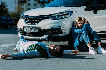 jeune femme assise près de voiture et en regardant blessé gisant sur la route après collision du trafic de peur